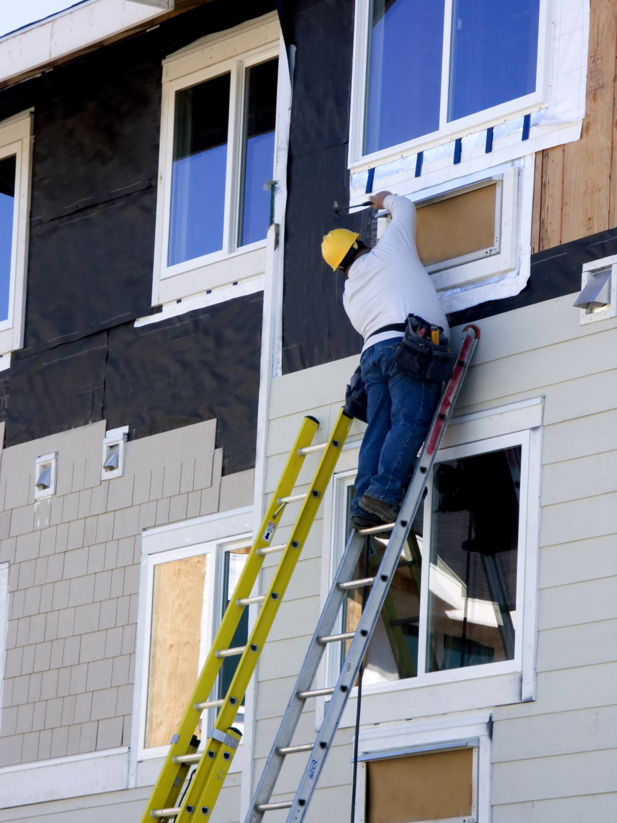 Consctruction worker hanging siding on new apartment building under consctruction.